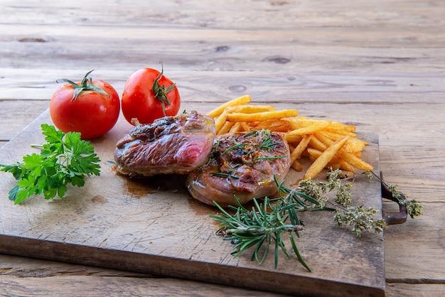 Ossobuco z indyka z grilla na desce do krojenia z frytkami i pomidorami