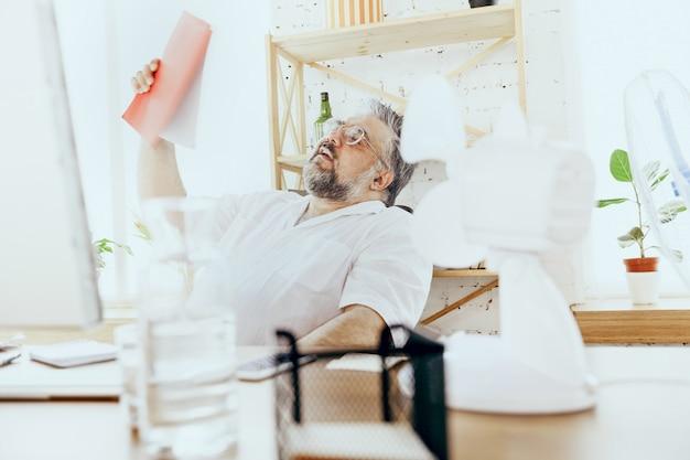 Ostateczny termin. biznesmen, kierownik w biurze z komputerem i wentylatorem ochładzającym się, uczucie gorąca, zaczerwienienie. używany wentylator, ale nadal cierpi z powodu niekomfortowego klimatu w szafce. lato, praca biurowa, biznes.