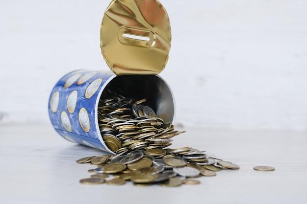 Ostatnie pieniądze w puszce mogą się zamknąć, wiele walut srebrnych i złotych monet rozłożonych na białym stole, ciężkie czasy i inflacja, kryzys finansowy