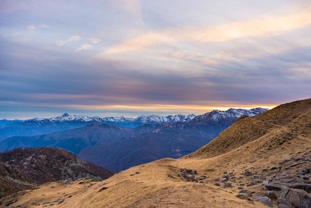 Ostatnie słońce w alpejskiej dolinie ze świecącymi szczytami górskimi i malowniczymi chmurami