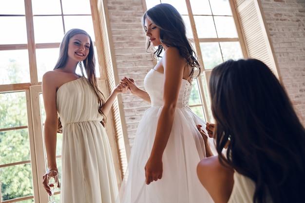 Ostatnie szczegóły. dwie atrakcyjne młode kobiety pomagają pięknej pannie młodej ubrać się