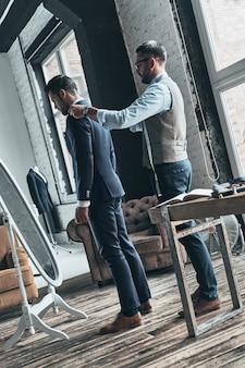 Ostatnie szczegóły. pełna długość młodego modnego projektanta pomagającego swojemu klientowi się ubrać