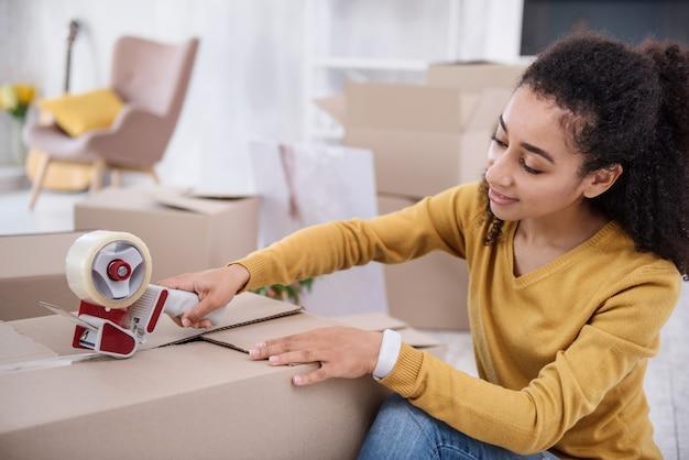 Ostatnie szczegóły. piękna dziewczyna z kręconymi włosami przygotowuje się do wyprowadzki z mieszkania i zaklejania pudełka rzeczami taśmą klejącą
