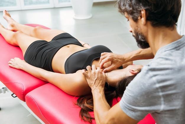 Osteopata przeprowadzający ocenę kości obojczyka, manipulujący palcami młodej kobiety na kanapie w swojej klinice