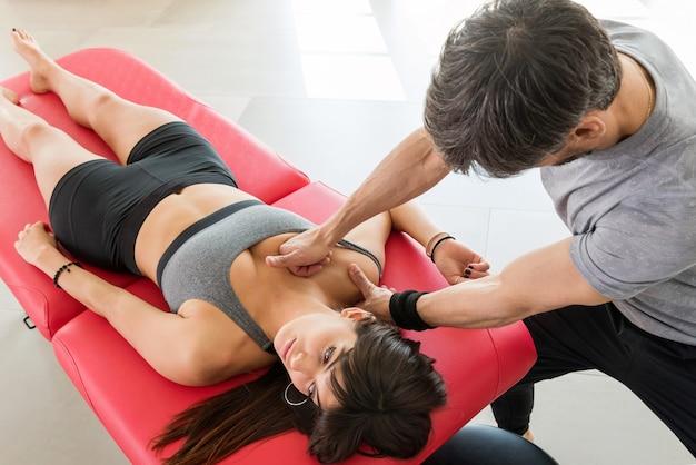 Osteopata wykonujący masaż mięśniowo-powięziowy mięśni piersiowych na młodej kobiecie za pomocą rąk do manipulowania mięśniami w koncepcji opieki zdrowotnej lub odnowy biologicznej
