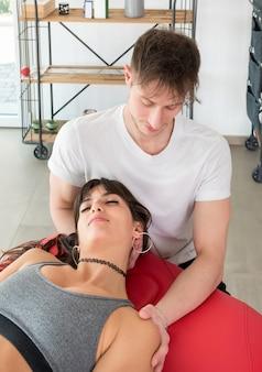 Osteopata wykonujący masaż mięśniowo-powięziowy mięśnia czworobocznego na młodej kobiecie manipulującej mięśniami rękami