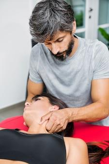 Osteopata wykonujący masaż mostkowo-obojczykowo-sutkowy mięśnia szyjnego