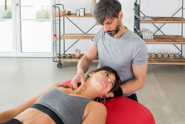 Osteopata wykonujący masaż mostkowo-obojczykowo-sutkowy mięśniowo-powięziowy u młodej kobiety, która manipuluje mięśniami szyi palcami, aby złagodzić ból