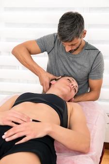 Osteopata wykonujący terapię zaufania szyjki macicy młodej kobiecie