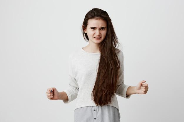 Ostra i wściekła brunetka modelka w przypadkowych ubraniach, z irytacją trzyma pięści, marszczy brwi, zaciska białe zęby z wyrazem zadowolenia. negatywne emocje, uczucia i reakcje