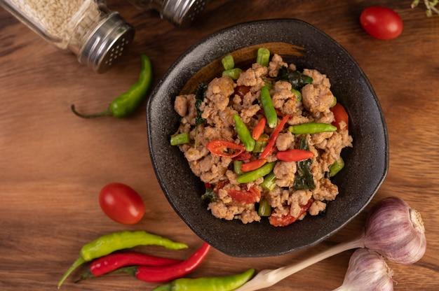 Ostra mielona wieprzowina i ryż na czarnym talerzu.