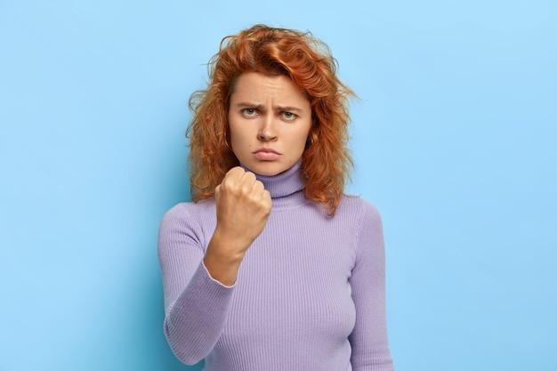 Ostra niezadowolona, poważna ruda dziewczyna pokazuje zaciśniętą pięść z gniewu, gotowa na każde wyzwanie