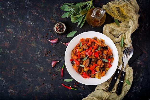 Ostra pikantna bakłażan, słodka papryka, pomidor i kapary. leżał płasko. widok z góry