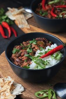 Ostre chili con carne z mieloną wołowiną, warzywami, ryżem. całość zwieńczona papryczką chili. meksykańskie jedzenie smaczne i ostre.