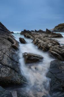 Ostre kamienie, skały obmywane przez fale zamazane.
