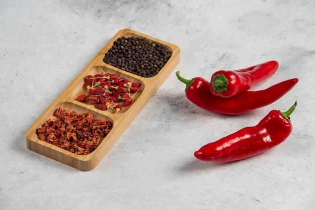 Ostre papryczki chili i przyprawy na marmurowym tle.
