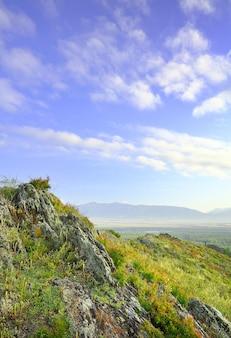 Ostre skały na szczycie góry nad górską doliną pod błękitnym pochmurnym niebem. syberia, rosja
