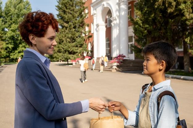 Ostrożna matka daje synowi papierową torbę z obiadem
