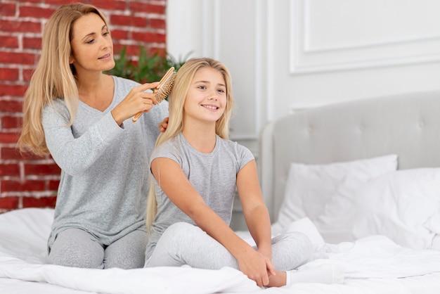 Ostrożna matka splata włosy córki