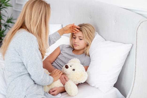 Ostrożna matka sprawdza córki temperaturę