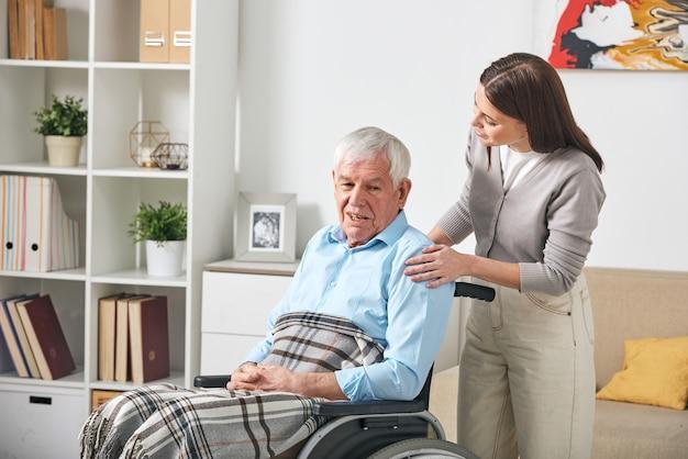Ostrożna młoda pielęgniarka rozmawia ze starszym mężczyzną na wózku inwalidzkim podczas wizyty w domu