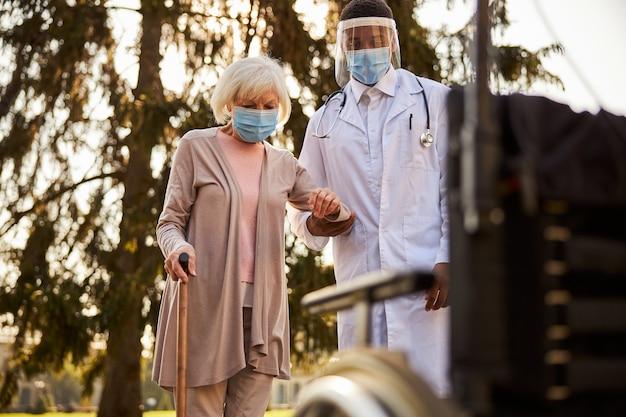 Ostrożna osoba medyczna z osłoną twarzy i maską, wspierająca starszą kobietę w drodze na wózek inwalidzki