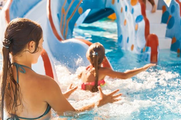 Ostrożna starsza siostra łapie swojego uroczego maleństwa, które zjeżdża po zjeżdżalni prosto do basenu i chlapie