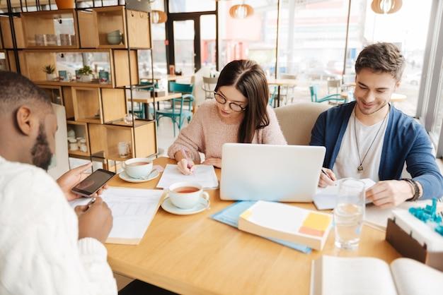 Ostrożne zadanie. trzech studentów z zagranicy bierze udział w procesie nauki siedząc w kawiarni.