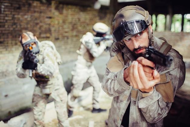 Ostrożni i profesjonalni zabójcy celują w różnych kierunkach. robią to spokojnie, ale pewnie. lider żołnierza ma w rękach pistolet.