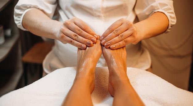Ostrożny masażysta dotyka nóg dziewczyny i masuje je roztworem