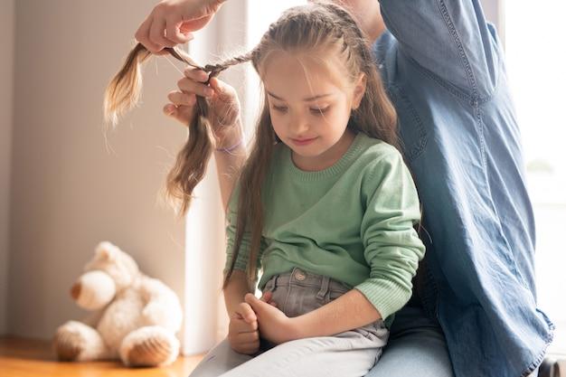 Ostrożny młody ojciec w dżinsowej koszuli splatania włosów córki, zdenerwowana dziewczyna siedzi na kolanach ojców i patrzy w dół