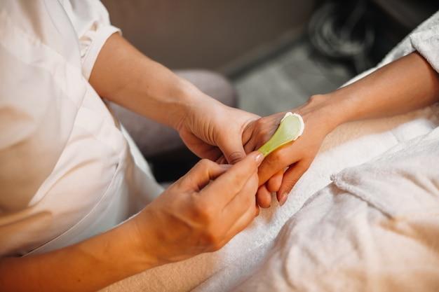 Ostrożny pracownik uzdrowiska nakłada na dłoń klienta krem przeciwstarzeniowy przed rozpoczęciem masażu