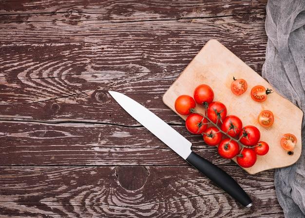 Ostry nóż i pomidory czereśniowe na desce do krojenia na powierzchni drewnianych