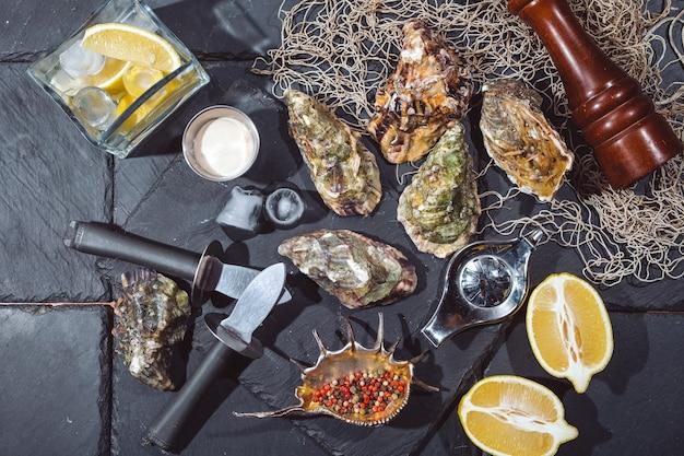 Ostrygi na kamiennym talerzu z lodem, cytryną, siecią rybacką, pieprzem i nożem.