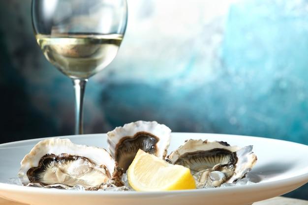 Ostrygi w białym talerzu z cytryną i lampką wina