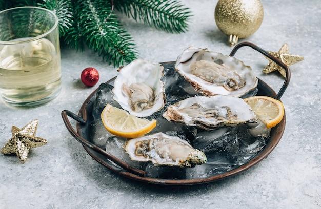 Ostrygi z cytryną, lodem i białym winem na betonowym tle z świątecznym wystrojem. obiad świąteczny