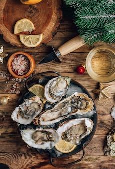 Ostrygi z cytryną na talerzu vintage na rustykalnym drewnianym tle z świątecznym wystrojem.