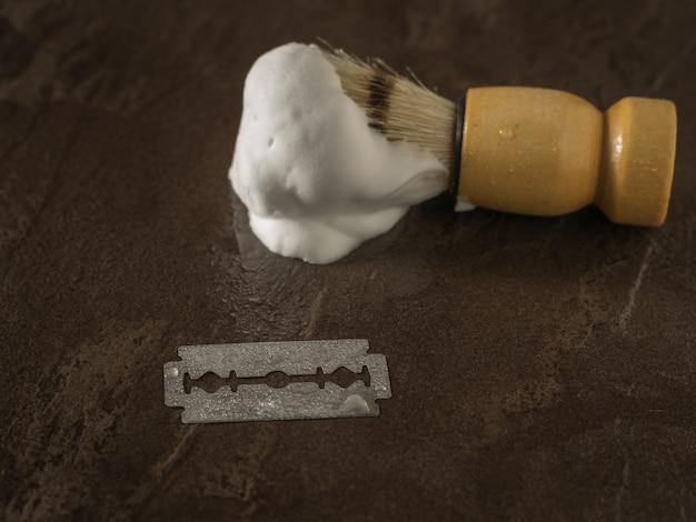 Ostrza pędzla do golenia z pianą na kamiennym stole. zestaw do pielęgnacji męskiej twarzy.