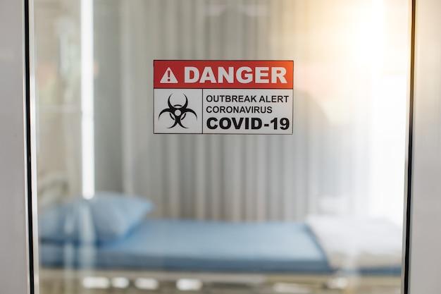 Ostrzeżenie o wybuchu epidemii wirusa koronowego zcovid19x znak na sali szpitalnej. puste łóżko szpitalne na tle.