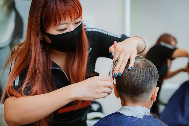 Ostrzyż dziecko klientowi za pomocą środków bezpieczeństwa. azjatycka fryzjerka. wznowienie pracy ze środkami bezpieczeństwa dla zakładów fryzjerskich w kontekście pandemii covid-19