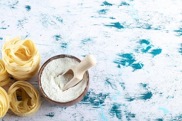 Osusz gniazda tagliatelle i miskę mąki na kolorowej powierzchni.