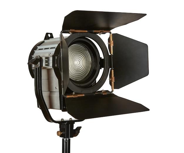 Oświetlacz światła stałego z zasłonami i soczewką fresnela na statywie do filmowania filmów. urządzenie jest izolowane na białym tle.