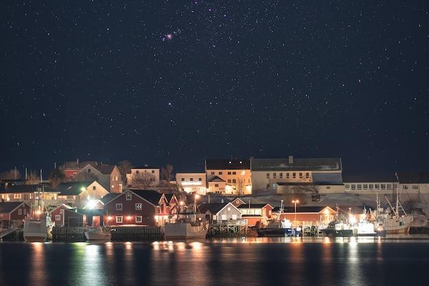 Oświetlenie norweskiej wioski z łodzi rybackiej na wybrzeżu z gwiazdami na nocnym niebie. lofoty, norwegia