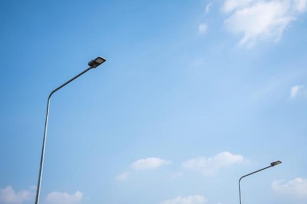 Oświetlenie uliczne led na stalowym słupie z niebieskim niebem i chmurą.