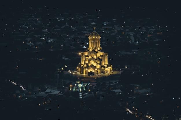 Oświetlona gruzińska katedra tsminda sameba w nocy w tbilisi, gruzja