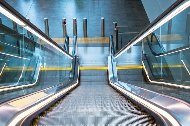 Oświetlona neonami metalowa koparka ze schodami z gumowymi poręczami zjeżdża na dół.