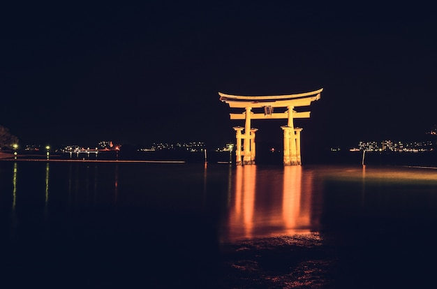 Oświetlona pływająca brama torii w nocy itsukushima, miyajimacho, japonia
