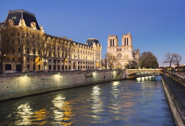 Oświetlona sekwana i katedra notre-dame wczesnym wieczorem.