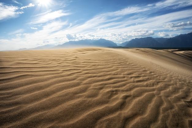 Oświetlona słońcem pustynia transbaikal z falistym wzorem z wiatrów na tle góry kodar