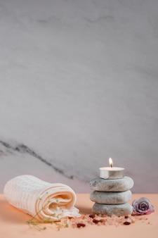 Oświetlona świeca nad kamieniami spa z serwetką; róża i sole himalajskie na brzoskwiniowym tle kolorowe na szarym tle